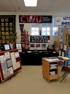 Image of a display booth with a tactile map on an easel to the left, a table in the center and a small desk covered in papers on the right,   There is a CWU banner and Central Access sign hanging on the wall over the table.