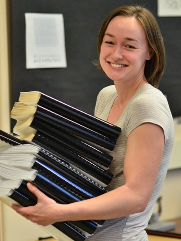 Smiling, female student technician holding a stack of braille volumes