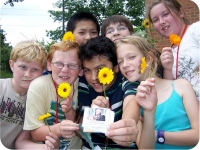 Campers showing off flower samples collected during an activity.