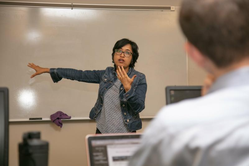 A college instructor speaks to adult students while pointing to a white board behind her and emphasizing her words with a gesture of her left hand.