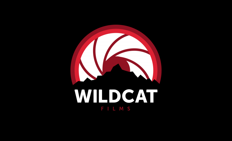 Wildcat Films logo displays the words Wildcat and Film underneath an outline of the Cascades mountains before a rising sun that looks like a camera lens's shutter partially open.