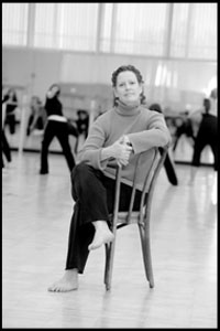 Therese Young sitting on a chair with dancers in background