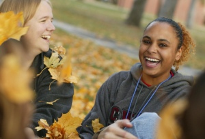 Picture of happy students enjoying autumn leaves