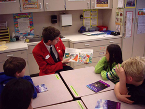 Student reads a book to children