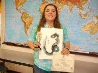 Lauren Gilmore holding her winning entry to the Bridges Chinese Culture Compitition along with certificate and trophy.
