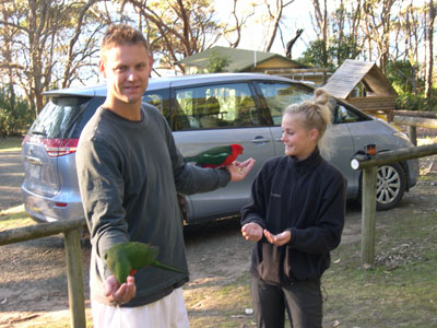 Son holding birds in both hands while daughter looks on