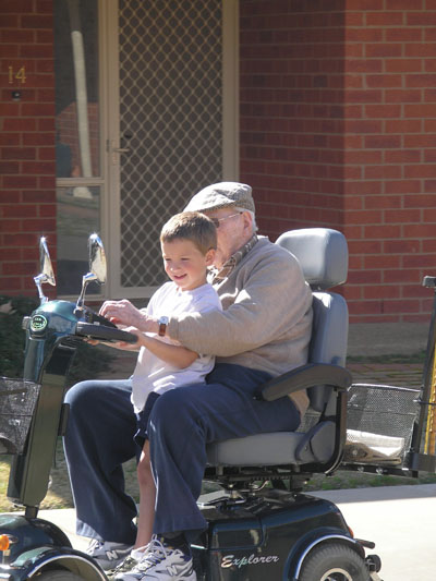Grandpa riding wheelchair with grandson in lap