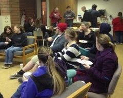 History students and other attendies chat, mill about and devour food before the talk.