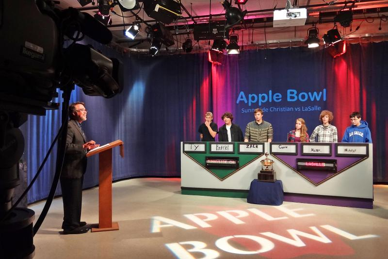 Apple Bowl host Pedro Bicchieri takes to the lectern just before a new game begins.
