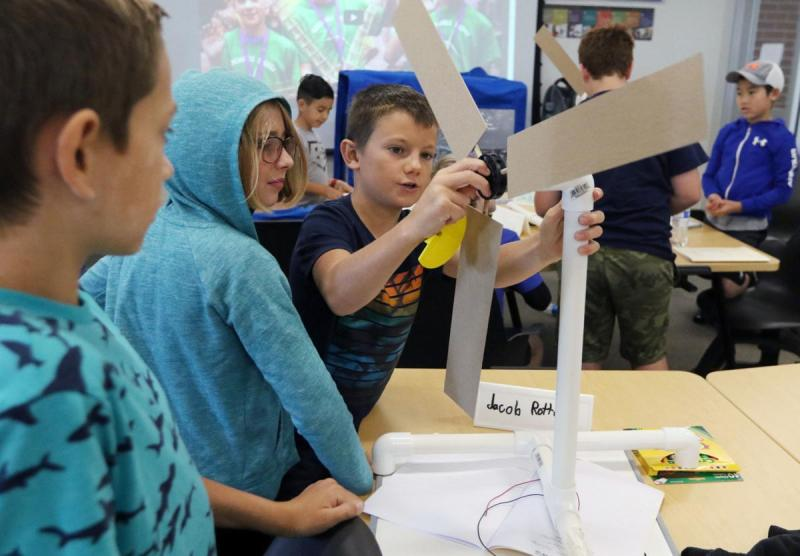 Boy attaches blades to a wind turbine during the KidWind Project workshop at CWU